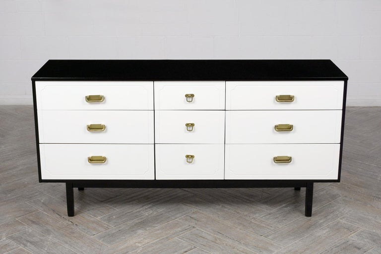 This 1960s Mid Century Modern Dresser has been fully restored is made from solid wood stained in a white & black color combination with a newly lacquered finish. The commode features nine drawers with brass polished pull handles, each side has three