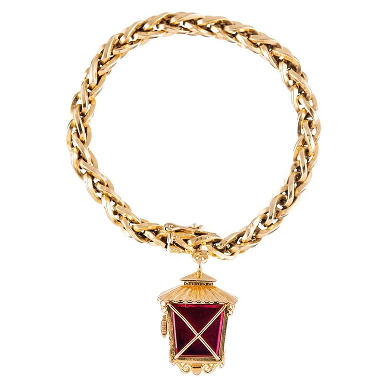 Vintage charm abounds... A truly unique twist on a classic charm bracelet, with an asymmetrical lantern-shaped manual wind watch suspended from a bracelet of 18 karat yellow gold links. Note the red enamel back and the textured honeycomb dial of the
