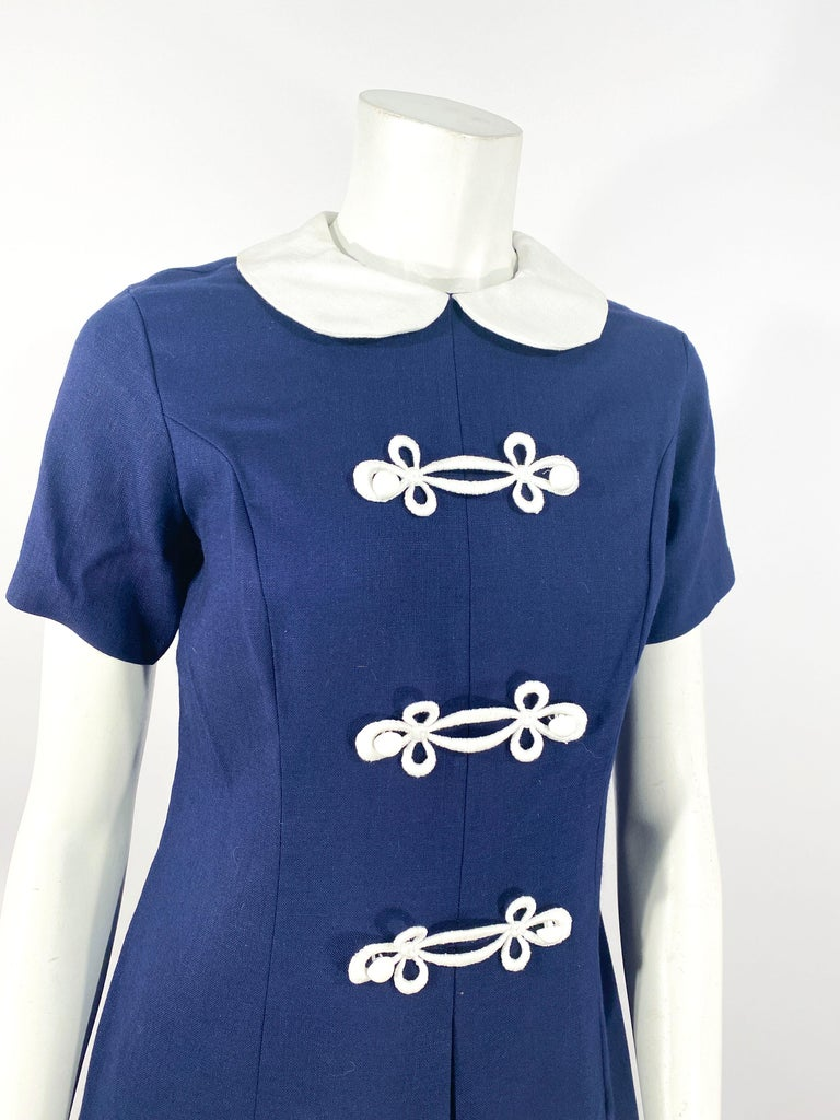 1960s Lanz navy mini shift dress with a white peter pan collar, white double frogs, and white dome button. The front of the dress has a wide kick pleat. Since the waist has a shift shilouette, the waist measurement accommodates smaller sizes.