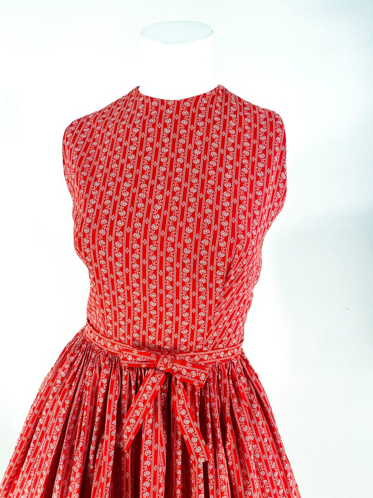 1960s Lanz red cotton dress featuring a fine calico print with heart-centered flowers, fitted sleeveless bolide, high neckline, keyhole back, seashell button closure on back of dress, and a gathered full skirt. This dress has been styled and