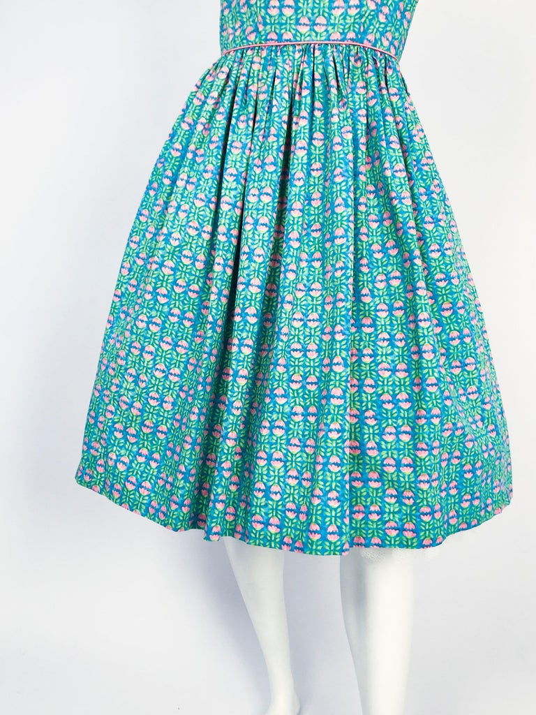1960s Lanz Tulip Printed Summer Dress. The base color is an aqua blue that has baby pink tulips and green leaves. The dress has a fitted bodice with a full skirt (photographed with a petticoat that is not included), pink border trimmings, and
