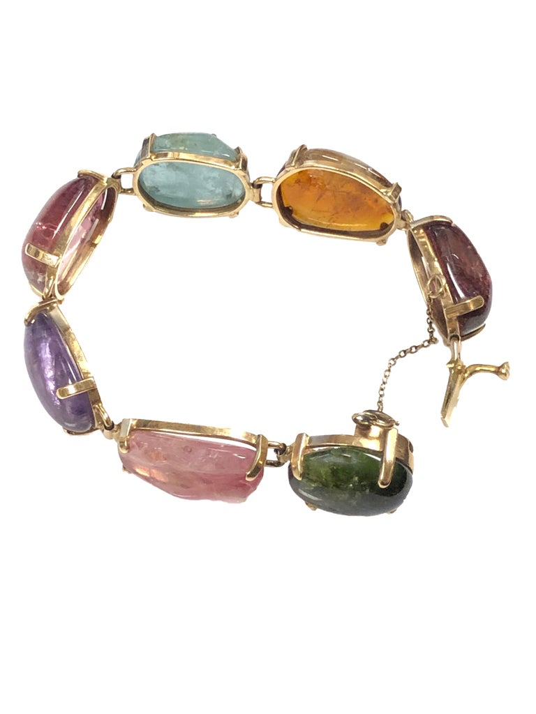 Circa 1960s 14K yellow Gold Bracelet Set with Large Cabochon Gem Stones in the style made famous by Seaman Schepps, the bracelet measures 7 1/2 inches in length 5/8 inch wide and is set with Tourmaline, Aquamarine, Amethyst, Garnet, Citrine, Peridot