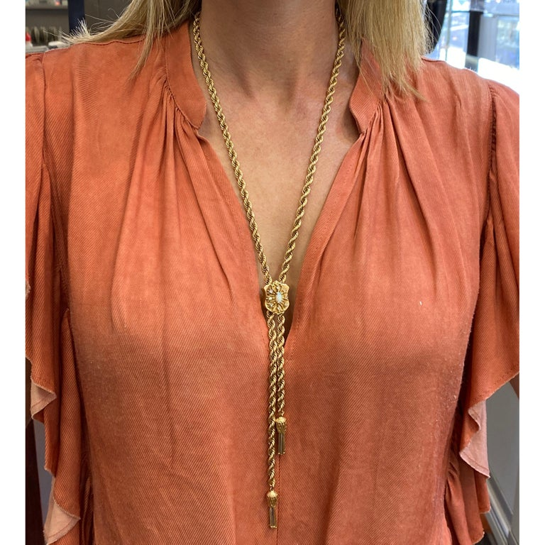 Diamond and opal lariat rope necklace fashioned in 14 karat yellow gold. The lariat features an opal and 8 single cut diamonds weighing .24 carat total weight and graded H-I color and VS clarity. The adjustable necklace measures 30 inches in length