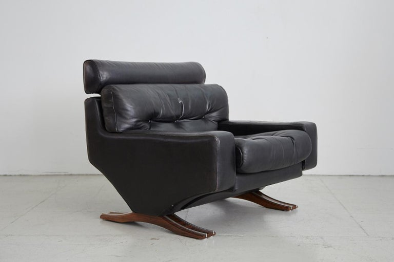 Handsome Italian leather armchair with original black leather cushioned seat resting on rosewood and aluminum legs. Great tufting detail and extremely comfortable.