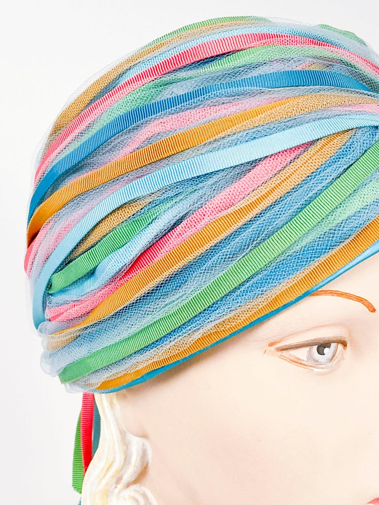 1960s light blue turban with gros-grain ribbon finishings in blue, light blue, lime, and hot pink gathered at the back with short tails. The base is made of a light blue netting and finished with satin.