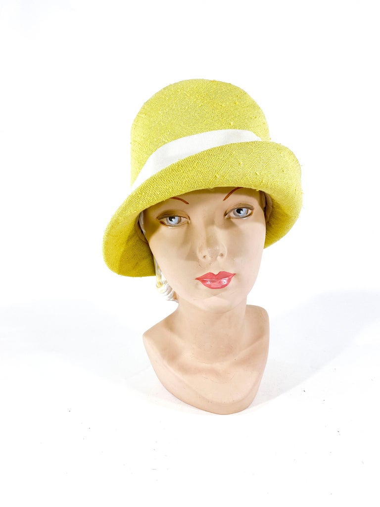 1960s Lilly Dache yellow-green linen hat with a grosgrain designer band and accent button.