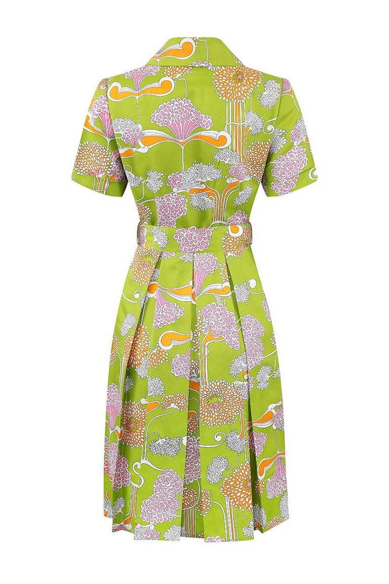 This vibrant late 1960s or early 1970s psychedelic print shirt dress is Gold Label by London Boutique Tricoville and is in exceptional vintage condition with some smart, striking design features. The silky feel fabric is a dynamic lime green with a