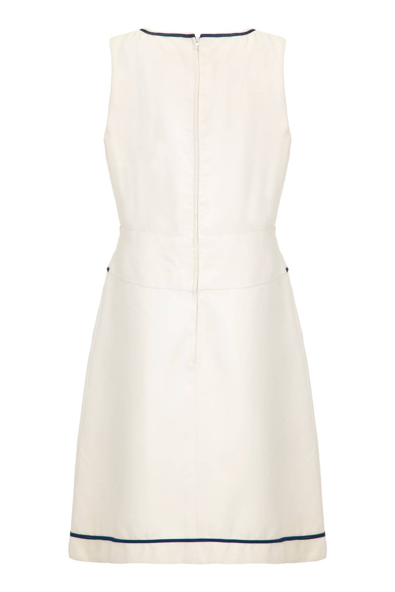 This desirable 1960s off-white mini dress by Louis Feraud for Rembrandt is in pristine vintage condition and superbly adaptable with a smart contemporary aesthetic. Made of thick nylon crepe fabric, the dress is sleeveless, tailored snugly over the