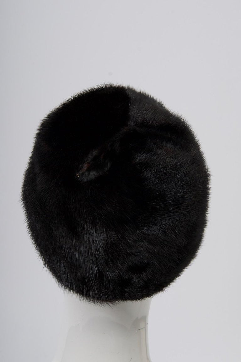 Dark mahogany mink skins distinguish this hat, finished on top with the subtle touch of a small claw. Lined with brocade, looks hardly worn. Retailed by Ohrbach's boutique Oval Room. Interior measurement 21.5