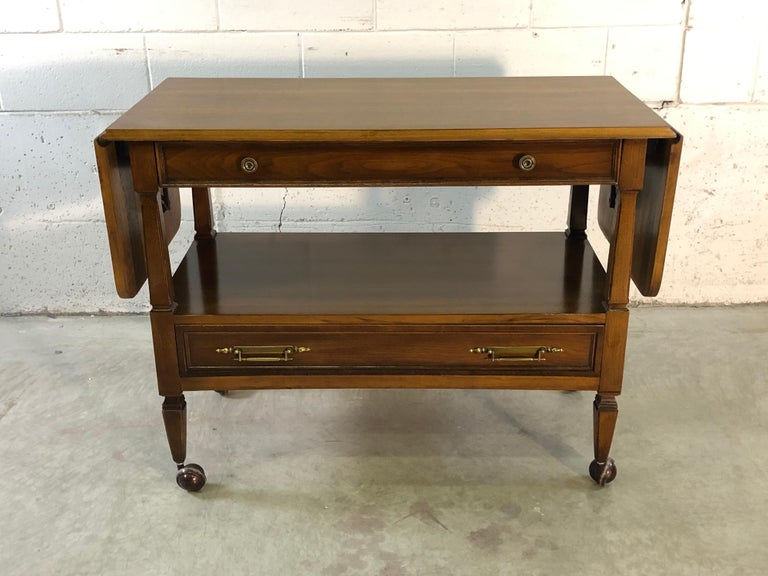 """Vintage 1960s mahogany wood rolling serving or bar cart. The cart comes with two drawers for storage. Measures: Fully open: 64"""" L. No marks. Newly refinished condition."""