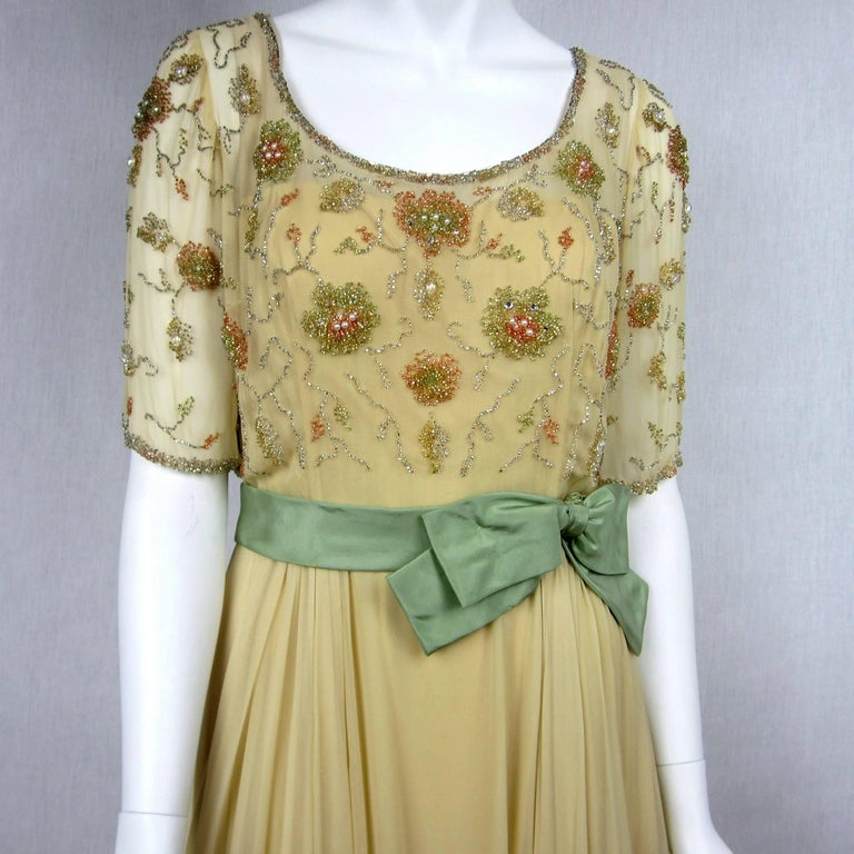 1960s Encrusted bodice made up of large oval beads and aurora borealis prong set Rhinestones as well as tiny bugle beads. Buttons up the back with a scoop necklace. Zippers up the waist. Loads of fabric make up the skirt. Wide Belt with side bow in