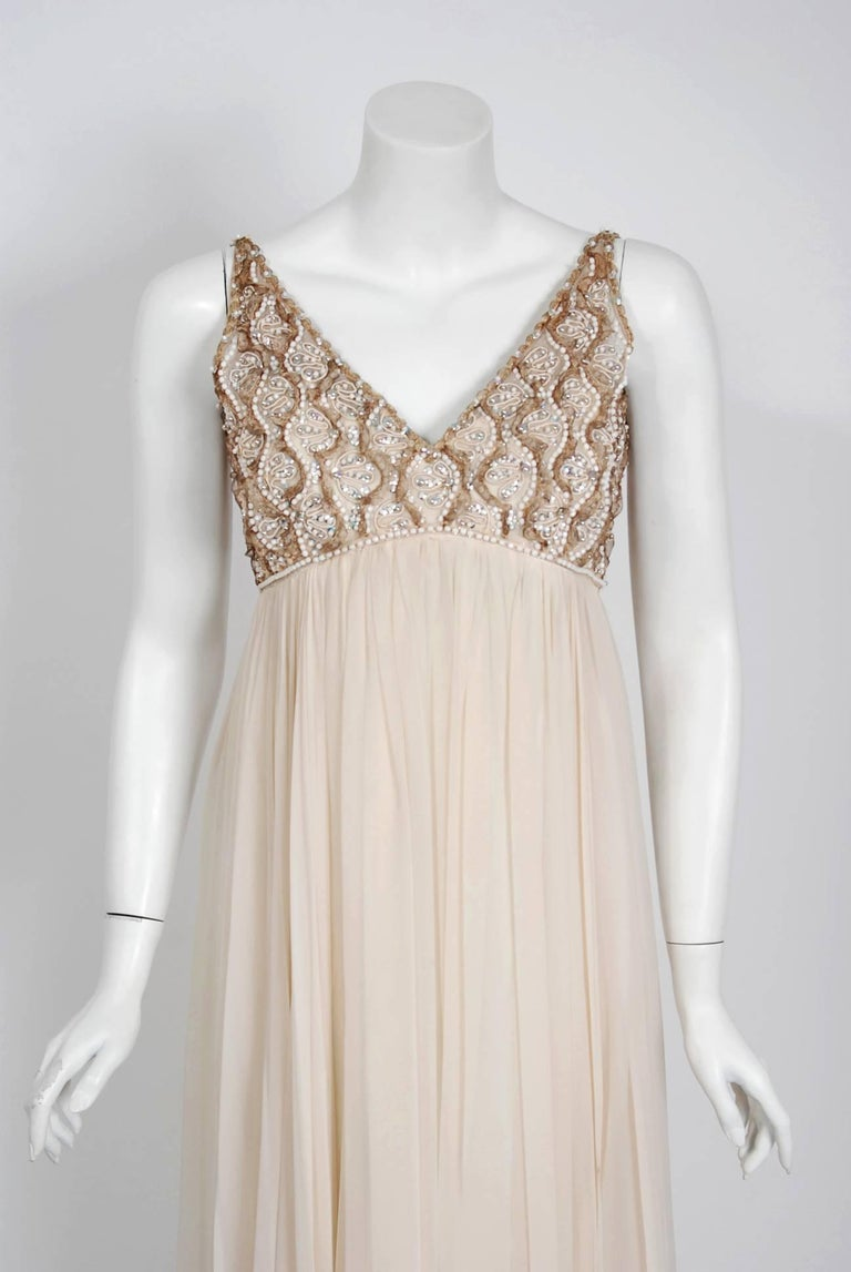 With the sparkling embellishment and ethereal ivory creme color, this dazzling 1960's Malcolm Starr evening gown does not disappoint. The substantial weight of the draped silk chiffon fabric whispers high-end luxury. The bodice is an elegant