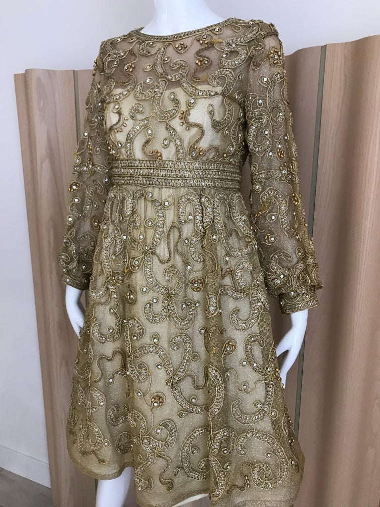 Vintage Malcolm Starr gold net overlay dress embellished with gold metallic braided ribbon and rhinestones.  Dress has Scoop neck, fitted waist, poet sleeves with gathered cuff, sequins and rhinestones . Dress is lined, zipper up the back, covered