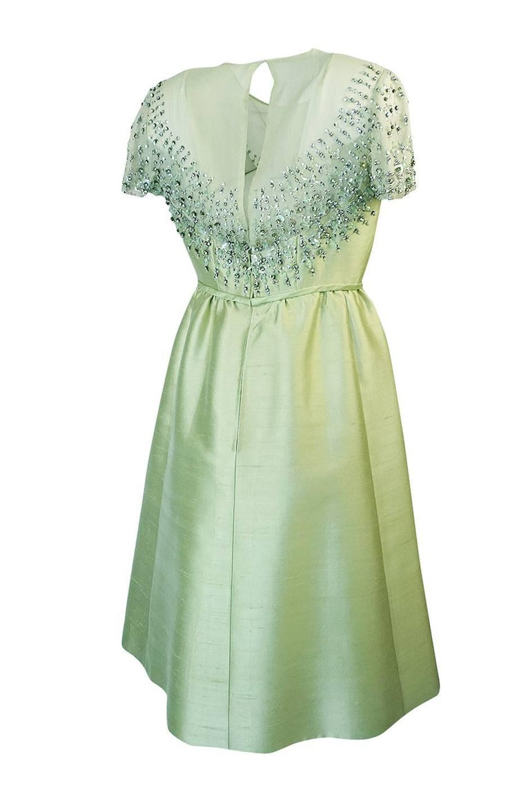 Elinor Simmons designed for the Malcolm Starr label from the early 1960s to 1972 and you can see her handiwork in this classic Starr piece with its almost sculptural lines and elaborate bead, sequin and rhinestone work. The dress itself has a
