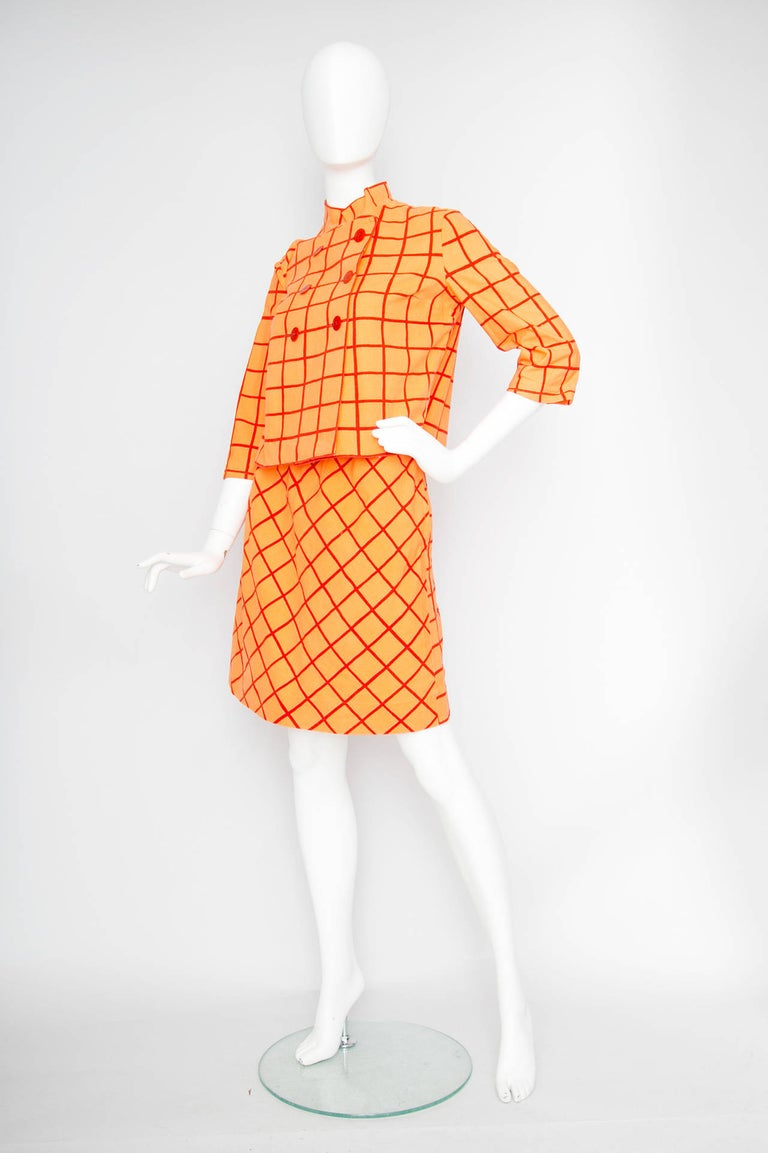 A lovely 1960s Marimekko two piece cotton color block ensemble in orange with bold red stripes. The ensemble features a cropped boxy jacket and an a-ilne miniskirt.   The double breasted jacket features a front wrap closure with six red buttons, a