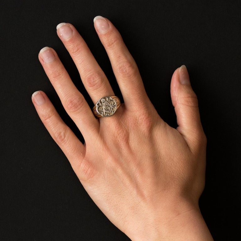 Ring in 14 karats yellow gold, and platinum. A man's signet ring, it is engraved on its plate with a pattern representing the Masonic symbols: the compass; the square and the G and set with a brilliant- cut diamond. The top, the bottom and the
