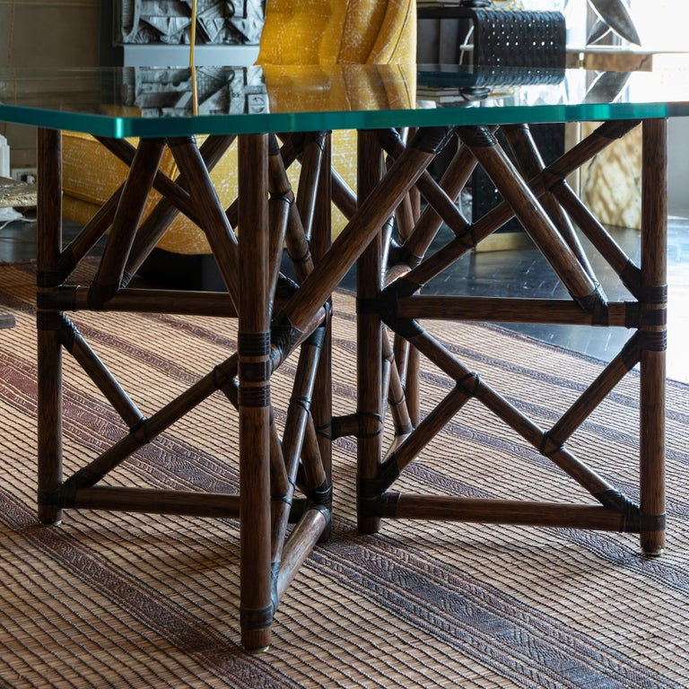 Modern bamboo rattan square dining table custom made by McGuire, base in bamboo rattan poles lashed with leather rawhide laces, original square tempered glass top, USA, circa 1960s.