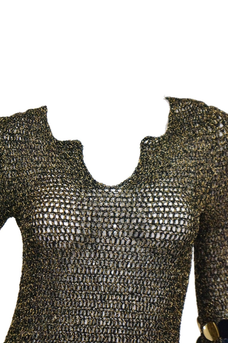 Sexy 1960s mini dress with metallic knit wear fabric. Dress has metallic gold and black pailletts  and a geometric/scoop neck line. Wear as a top or mini dress with or with out a silky slip.