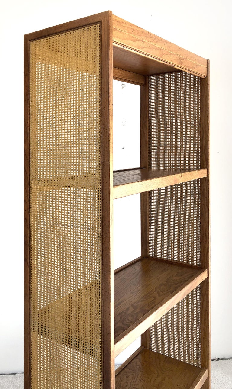 1960s Mid-Century Modern Dunbar style bookshelf  It is a sleek midcentury designed 4-shelf wooden bookcase with inset woven cane panels. The bookcase is created in the style of Dunbar Furniture.