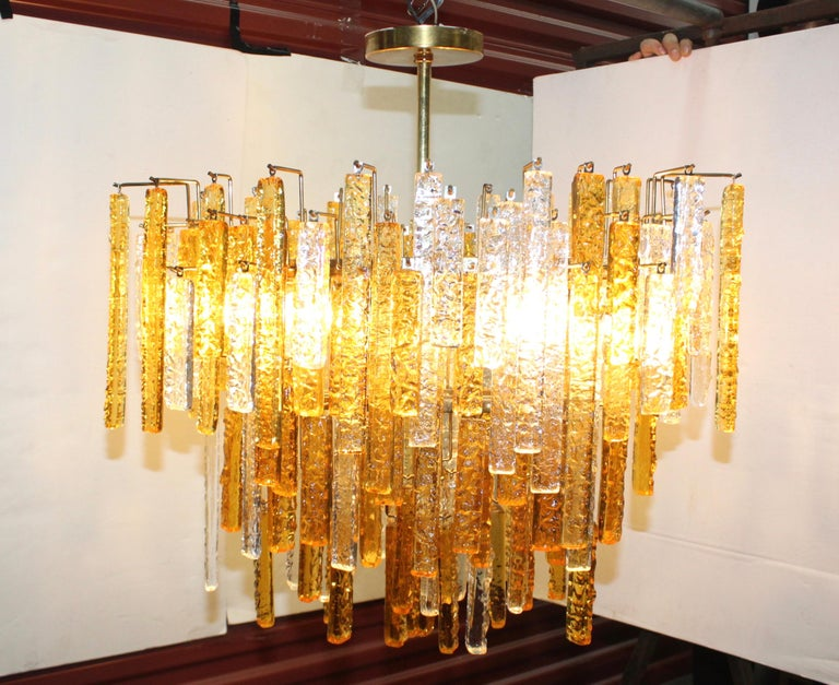 Stunning 1960s Mid-Century Modern Venini glass chandelier with brass frame and amber and clear glass rods.