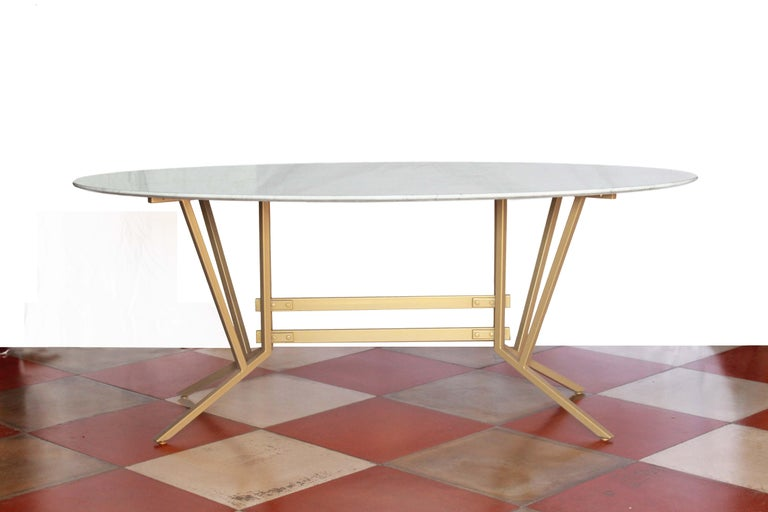 An elliptical dining table with Carrara marble top and champagne color iron structure. Suitable for 6 people. The Carrara top has been cleaned and polished whilist the iron structure has been repainted brand new. In excellent conditions.  NOTE: