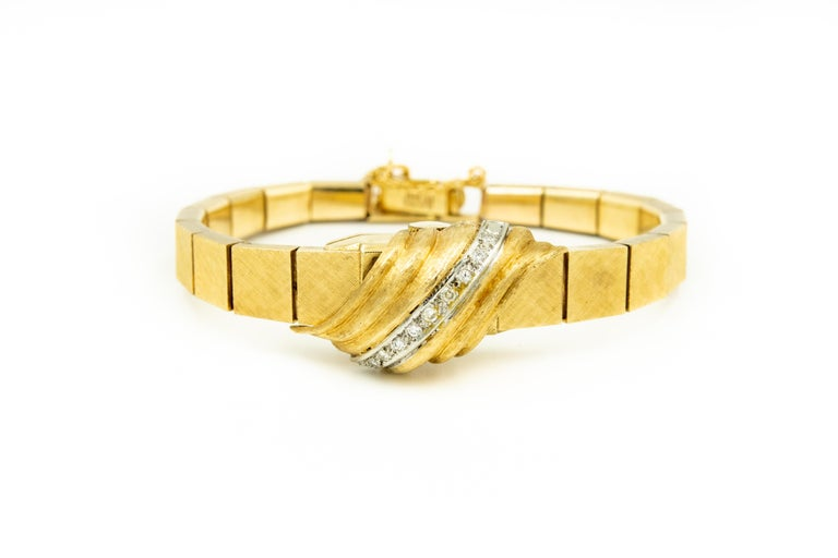 Mid 20th century 14k yellow gold watch with a diagonal row of 9 x .01 c. each single cut diamonds for an approximate total weight of  .09 carats.  The cover hinges up to reveal the time.  It has a mechanical movement which means you mush wind it