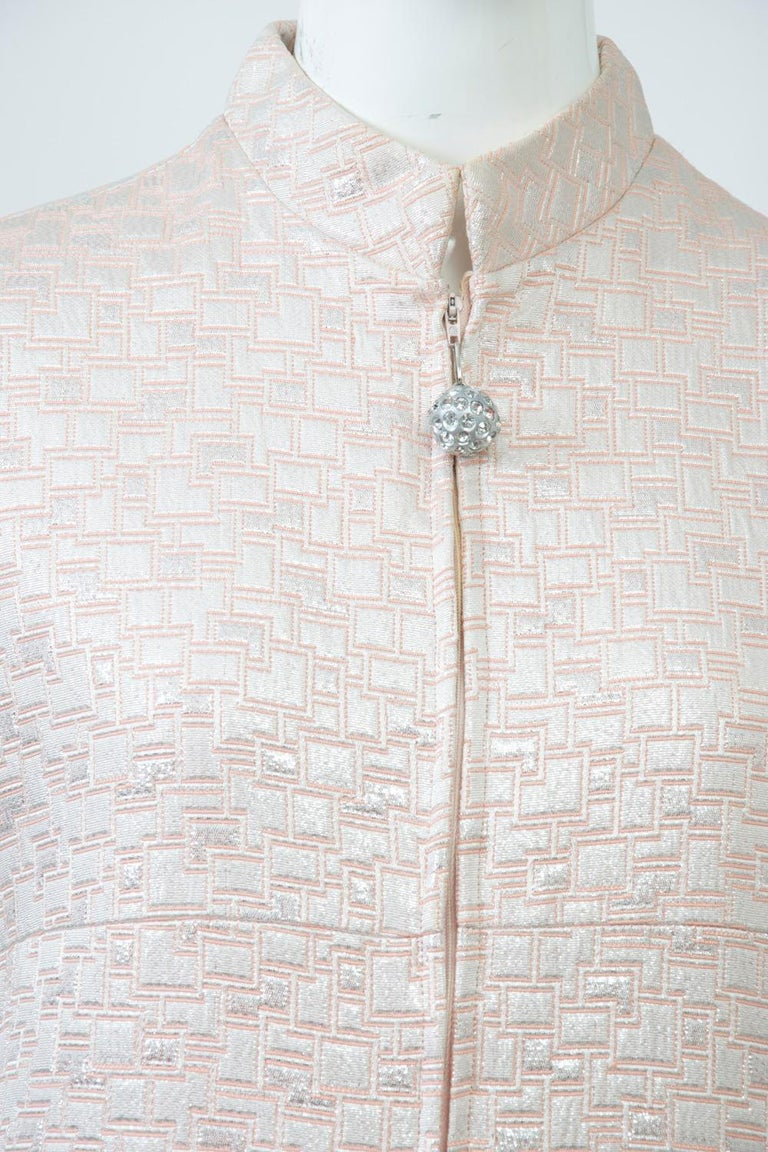 Don Sophisticates shift-style dress in silver and peach geometric brocade featuring a front zipper with rhinestone-ball pull up to its mock turtleneck, short sleeves, and small patch pockets; there is a seam under the bust that continues around the