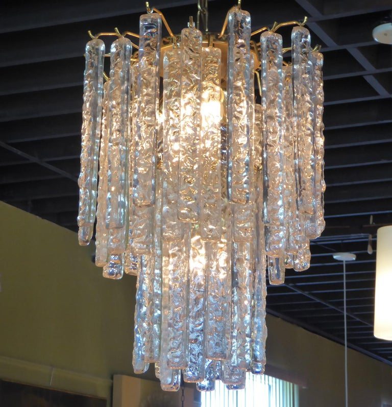 Draped with 54 long textured Murano crystals, this 1960s Mazzega Chandelier beautifully has four inner lights and a strong, solid brass frame, chain and canopy. The four sockets take medium base bulbs. Measurements: Fixture with crystals 22 inches