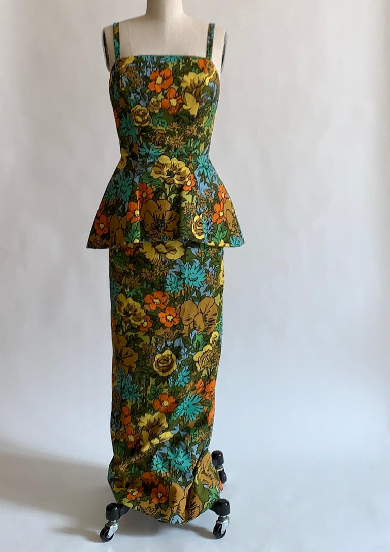 Stunning 1960s vintage Mr. Blackwell Custom floral print dress in vibrant shades of yellow, orange, brown, blue, and green. Peplum waist that feels like it must be enforced with horsehair.  Slit at center back. Two zips at back, with small bow