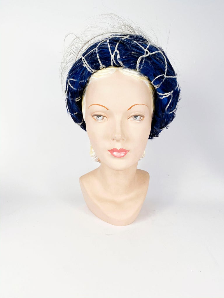 1960's Mr. John Blue feathered hat with silver mettalic netting and finished with a silver-colored whimsical feather accent.