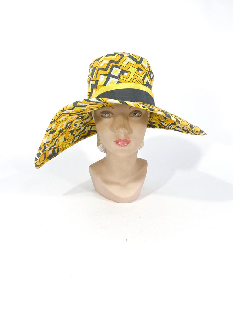 1960s in a 1920s style Mr. John Geometric printed hat with a wide asymmetrical brim. The print features yellow, white, grey , and gold. The hat band is two-toned in yellow and grey grosgrain ribbon accented with grey decorative buttons.