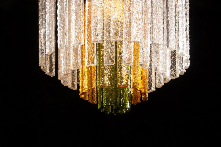Amazing Murano Venini chandelier. This wonderful lamp consists of a metal frame with 24 clear, 12 amber and 6 green Murano glass items. It is in a beautiful and working condition. Period 1960s Dimensions: H.55 cm, ø50 cm.