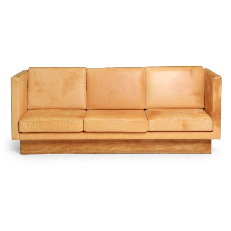 A superb high backed, substantial and well scaled sofa of spare rectilinear form having hand stitched natural leather cushions floating on a faux leather white oak plinth base.