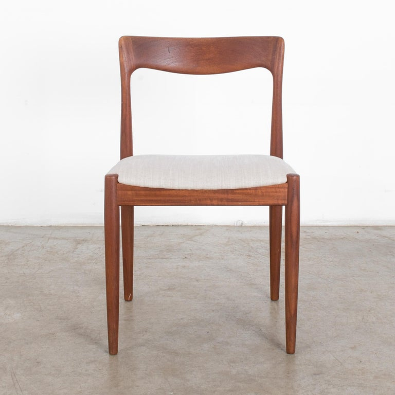 A 1960s teak chair by Danish furniture designer Neils O. Møller. A modernist design with tapered legs and fluid, expressive back piece. A cushioned seat is upholstered in a natural white. The warm, rosy tones of the teak emphasize the sophistication