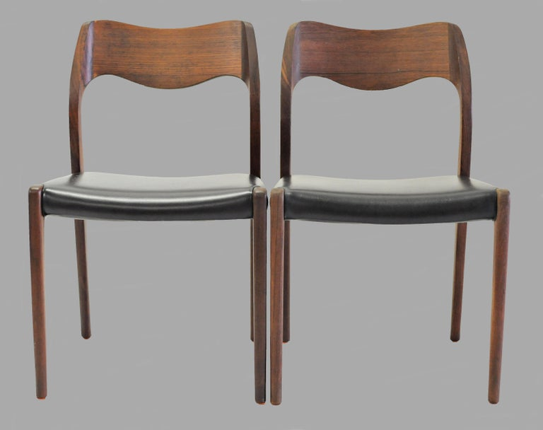 Set of 12 teak dining chairs designed by Niels Otto Møller in 1951.  The chairs feature a solid frame and backrest in teak designed with straight lined legs and an elegant organic shaped backrest with the soft lines and curves that you often see