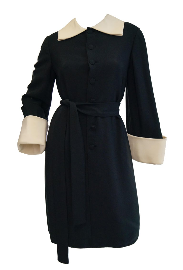 Spectacular shift dress by Norman Norell!  The drama of this dress makes one feel as though it is a coat, with its large cuffed sleeves and large collar. The fabric is black silk with a nice hand. It also has a belt to cinch in the waist. It is a