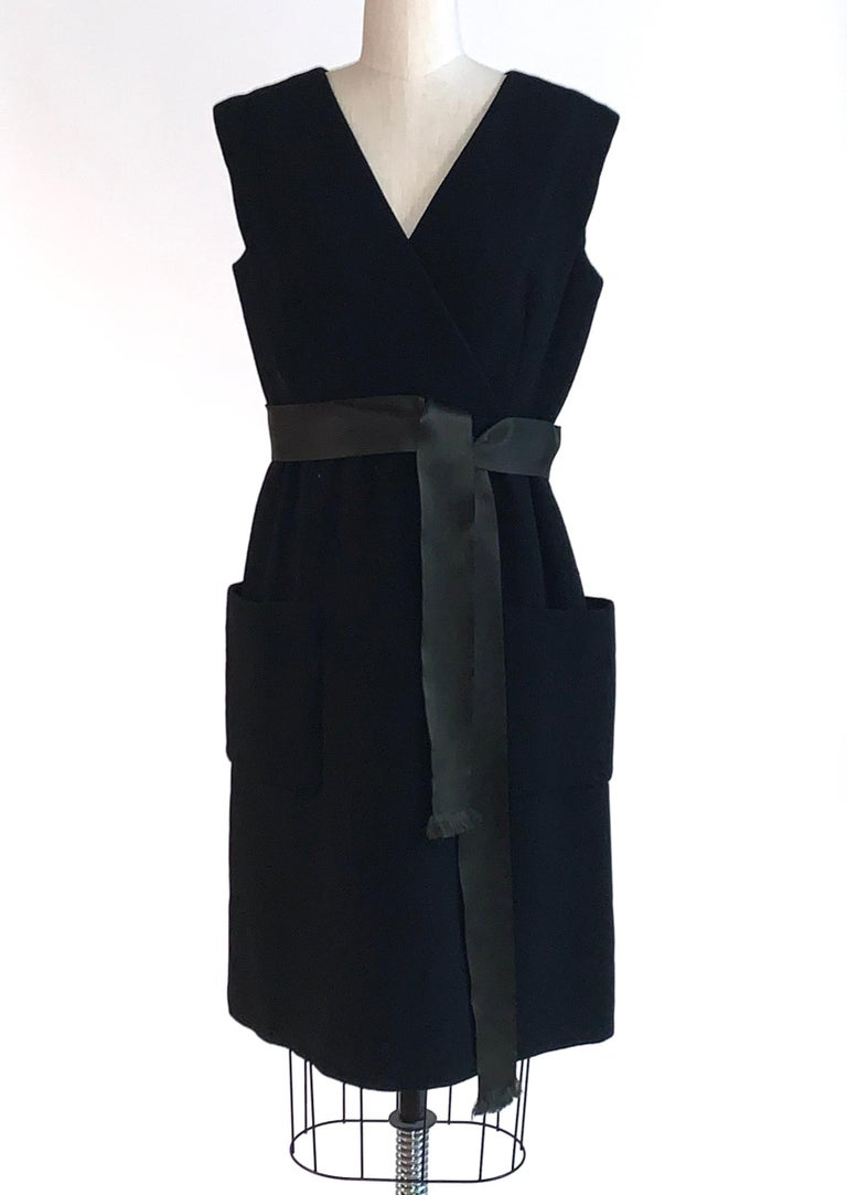 Vintage Norman Norell 1960s sleeveless little black dress with patch pockets at sides and ribbon sash at waist. crossover v neck detail at bust, and buttons up back of dress from middle. Keystone dress shields at inner underarms.   Labelled Norman