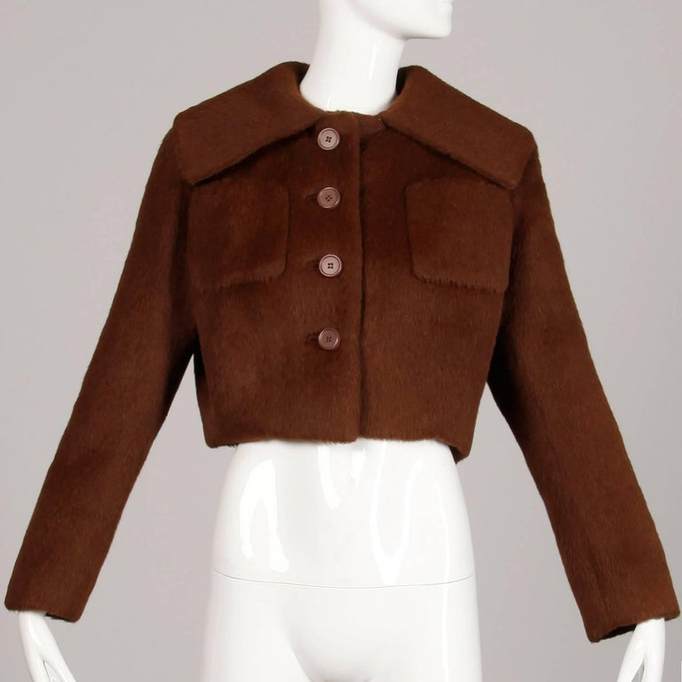 Absolutely stunning construction! Vintage 1960s Norman Norell brown wool jacket with a pop up portrait collar. Fully lined in silk with front button and snap closure. Front patch pockets. Fits like a size medium-large. The bust measures 44