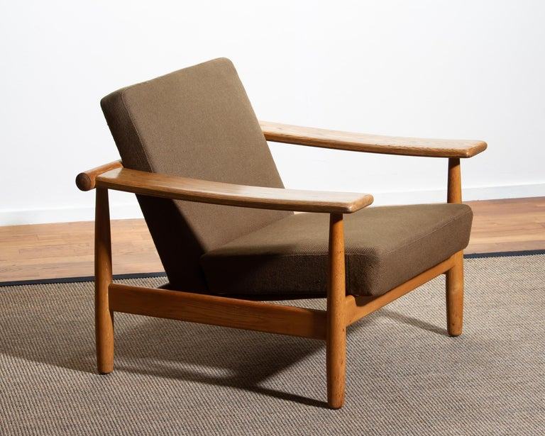 Beautiful oak lounge chair from the 1960s made in Denmark. The oak frame is in good condition.  The fabric is in fair condition like the pictures shows.  Also we have a suitable sofa in our gallery!