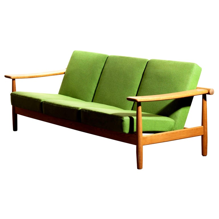 Beautiful oak sofa from the 1960s made in Denmark. The oak frame is in good condition. The green fabric is in fair condition like the pictures shows.