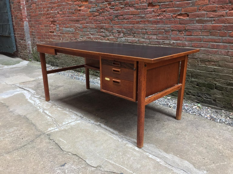 Solid oak frame with a black laminate top. Beautiful old growth tight grain. Three graduated drawers with many options due to the size of the flat surface, circa 1960. Original finish. Good condition with some minor light scratches on the black