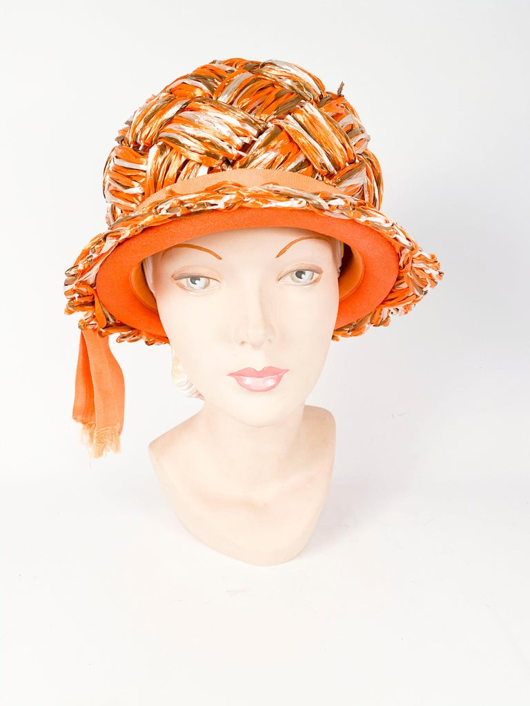 1960s Orange woven raffia hat with brown and beige accents in the weave. This hat is finished with a grow-grain ribbon and short fringed tails.
