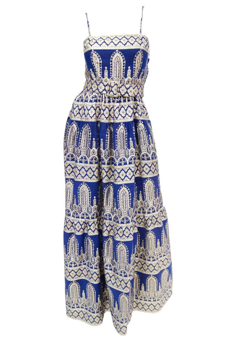 Amazing deep royal blue and metallic gold evening dress with matching jacket ensemble by Oscar de la Renta. The brocade dress is maxi length with an A - line skirt, fitted bodice, thin spaghetti straps, and a cinched waist accented by a wide belt