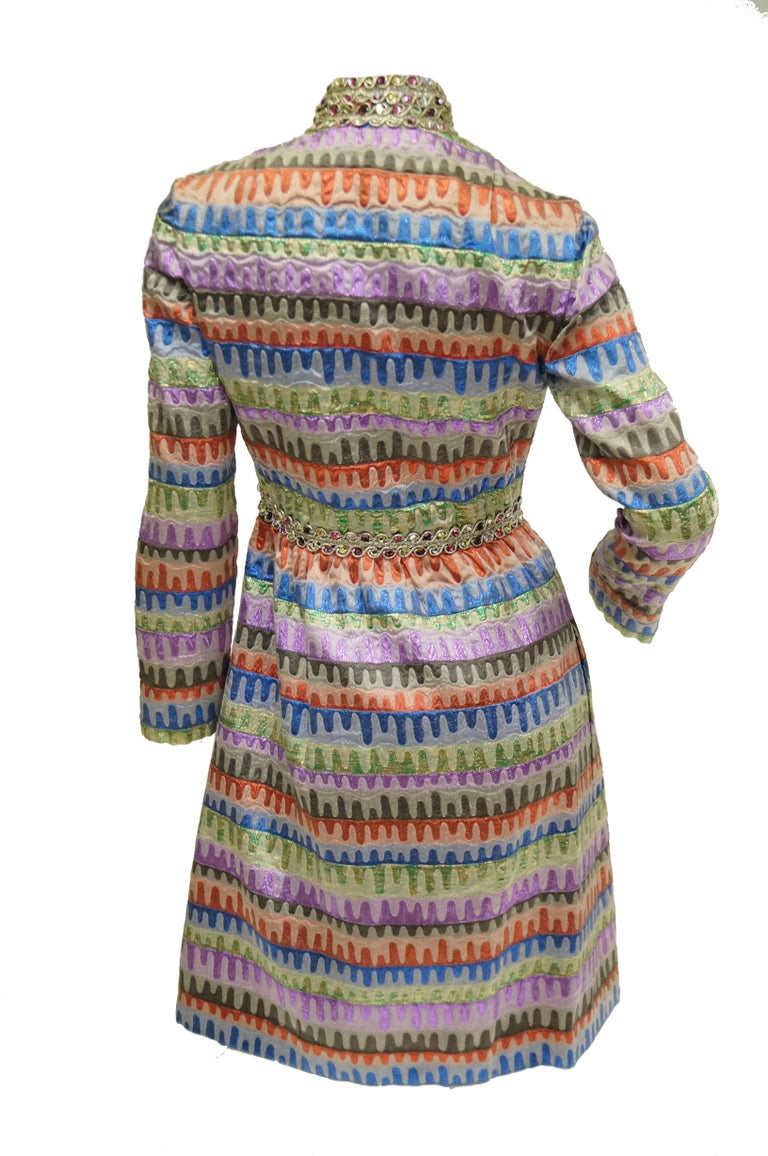 Simply stunning multicolor party dress by Oscar! This gloriously 60s piece features a knee - length hem, A - line silhouette, long sleeves, and mandarin collar. The dress is composed of an amazing brocade fabric with red, blue, green, purple, and