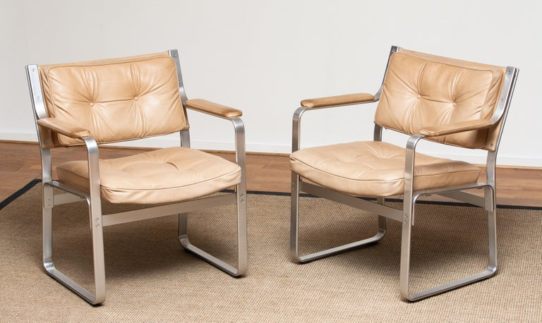 1960's set of two 'Mondo' armchairs in aluminum with beige / taupe leather upholstery designed by Karl Erik Ekselius for J.O. Carlsson / JOC design in Sweden. Both chairs are in perfect condition and completely original. The fillings in de seats
