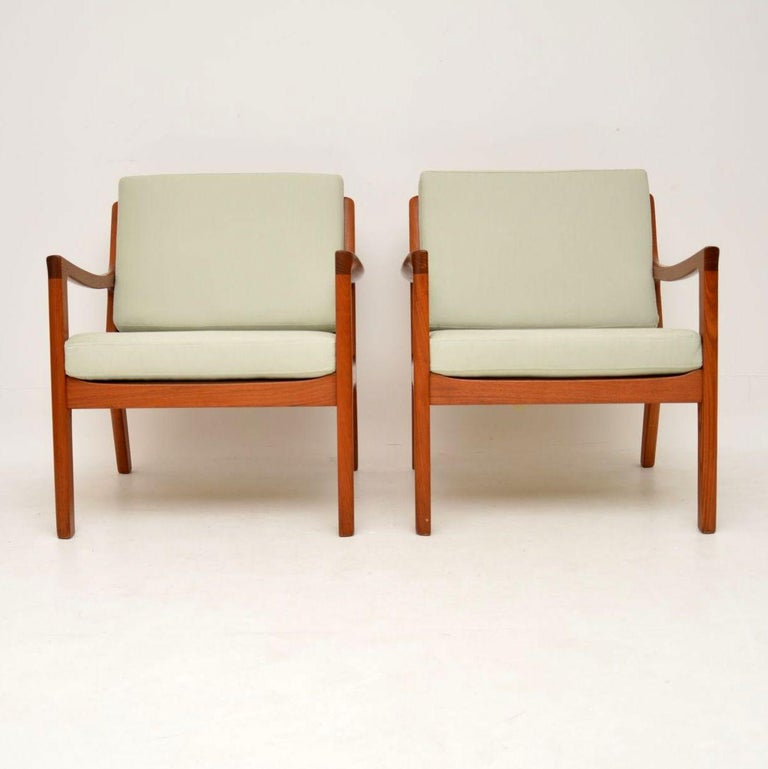 A stunning pair of Danish armchairs in solid teak, this model is called the 'Senator', it was designed by Ole Wanscher and was made by Cado in the 1960s-1970s. They are in excellent condition for their age, the teak frames are clean, sturdy and