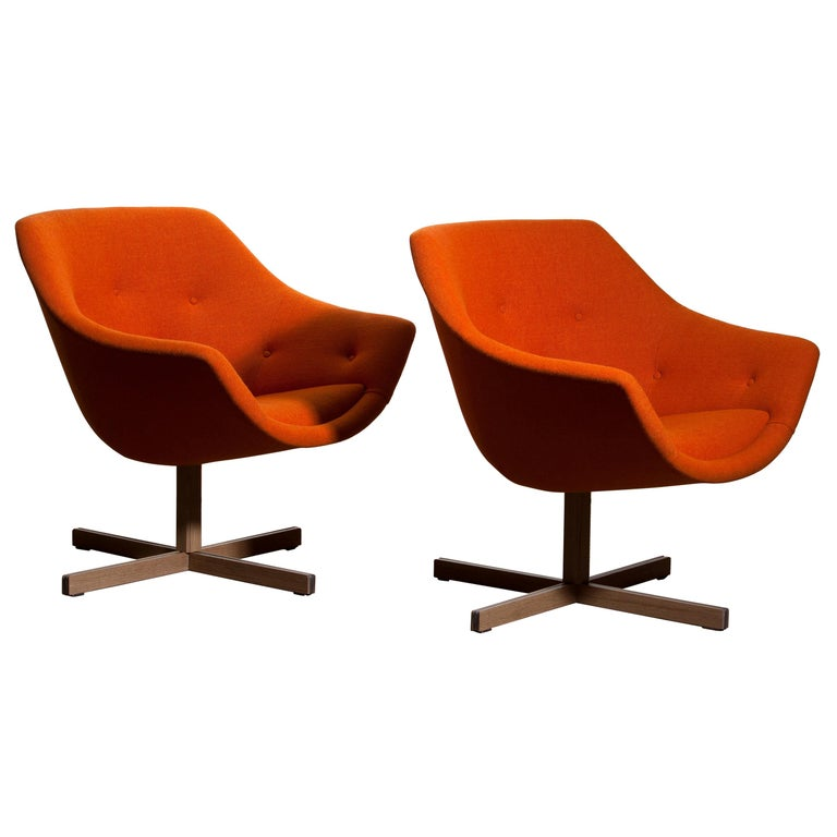Fantastic pair of 'Mandarini' swivel armchairs made by Carl Gustaf Hiort for Puunveisto Oy, wood work Ltd. These chairs are upholstered with a buttoned orange fabric 'Hallingdal' by Kvadrat designed by Nanna Ditzel, on an oak swivel base. They are