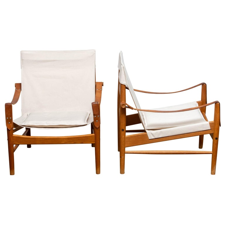 Beautiful pair of safari chairs designed by Hans Olsen for Viska Möbler in Kinna, Sweden. These chairs are made of oak with a new canvas upholstery. They are in a wonderful condition and marked. Period: 1960s. Dimensions: H 81 cm, W 73 cm, D 70