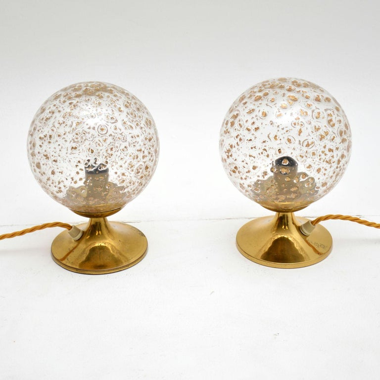 A beautiful and unusual pair of table lamps, these dates from the 1960s-1970s.  They have lovely spherical textured glass shades, and sit on brass bases. They are in great condition for their age, with no damage to be seen. There is just some