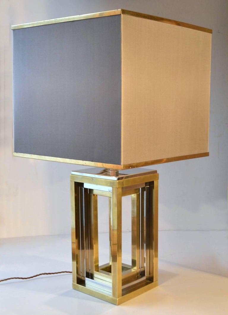 Large pair of geometrical Romeo Rega table lamps with frames in alternating brass and chrome square tubes. The original square taupe shades are edged with brass on the top and bottom. They are signed and in excellent vintage condition. They are